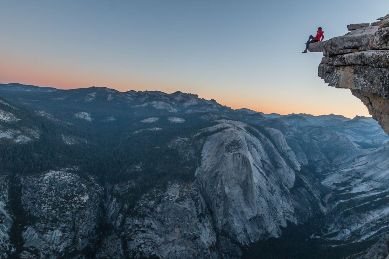 Eine Bergsteigerin ruht sich auf einer Klippe aus. Risikomanagement ist für sie privat und als Anlegerin ein Thema