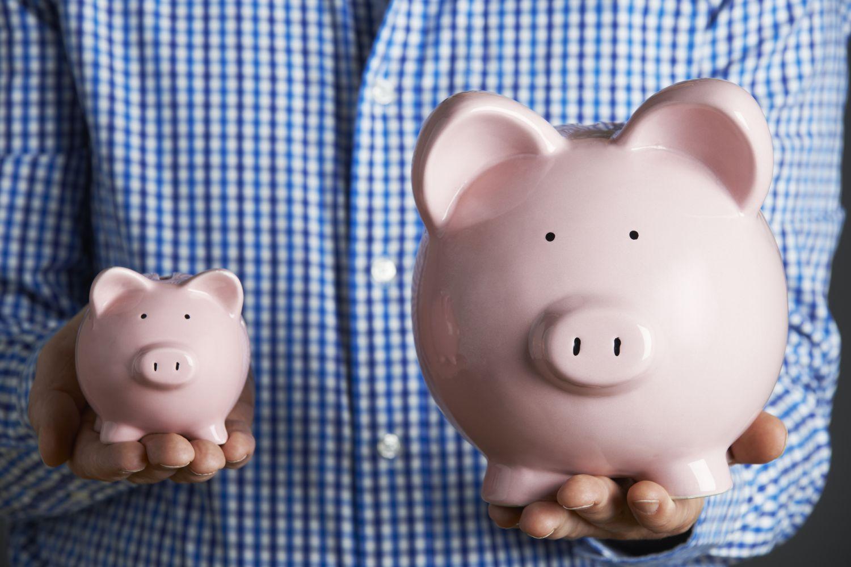 Ein Mann hält zwei Sparschweine in seinen Händen