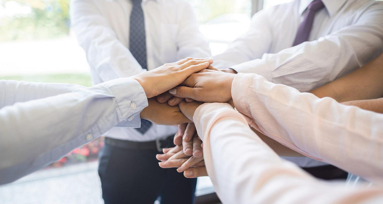 Mehrere Personen legen ihre Hände aufeinander (Symbolbild Zusammenhalt)