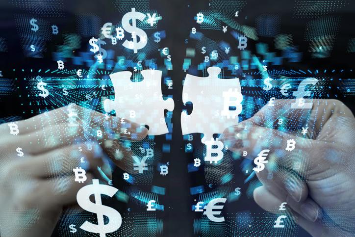 Hände halten zwei Puzzleteile nebeneinander. Darum herum sind verschiedene Währungssymbole angeordnet. Thema: Fintech-Unternehmen