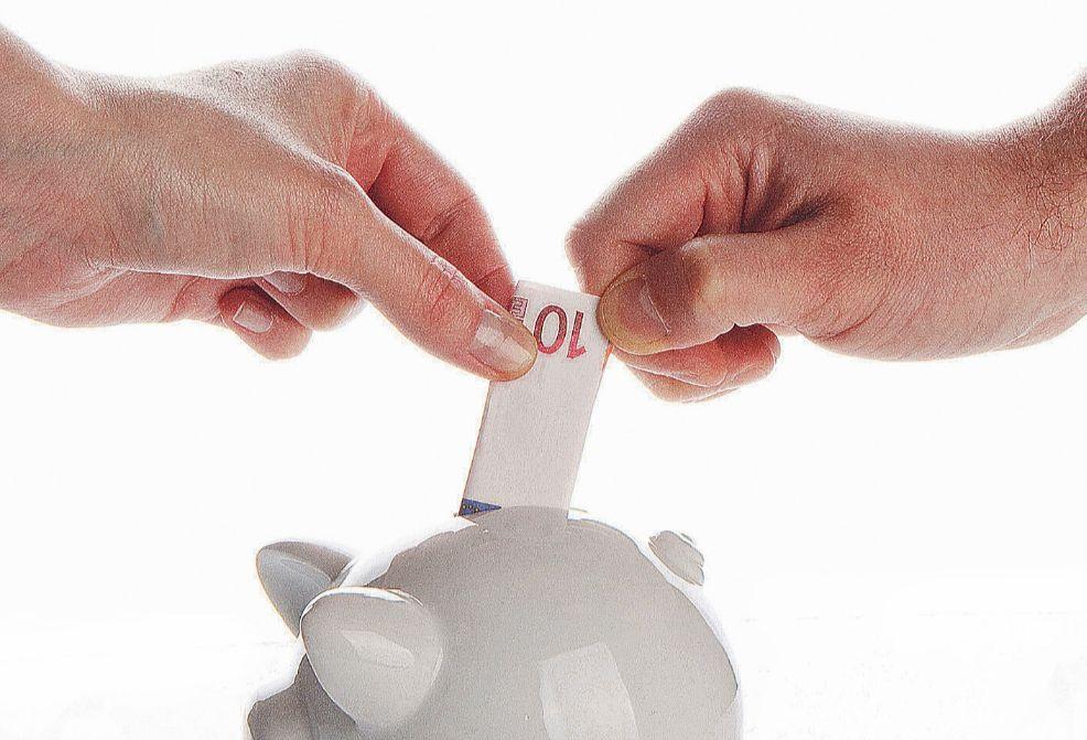 Frau und Mann stecken 10-Euro-Schein in ein Sparschwein