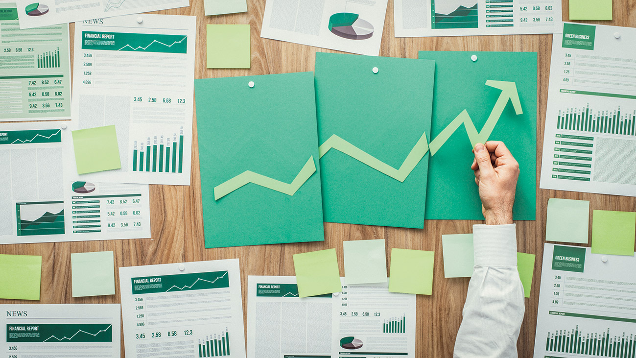 Grüne Unterlagen liegen auf einem Schreibtisch.