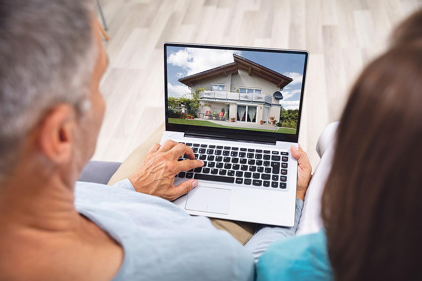 Ein Mann und eine Frau schauen sich Häuser im Internet an. Thema: Immobilienmarkt nach der Coronakrise