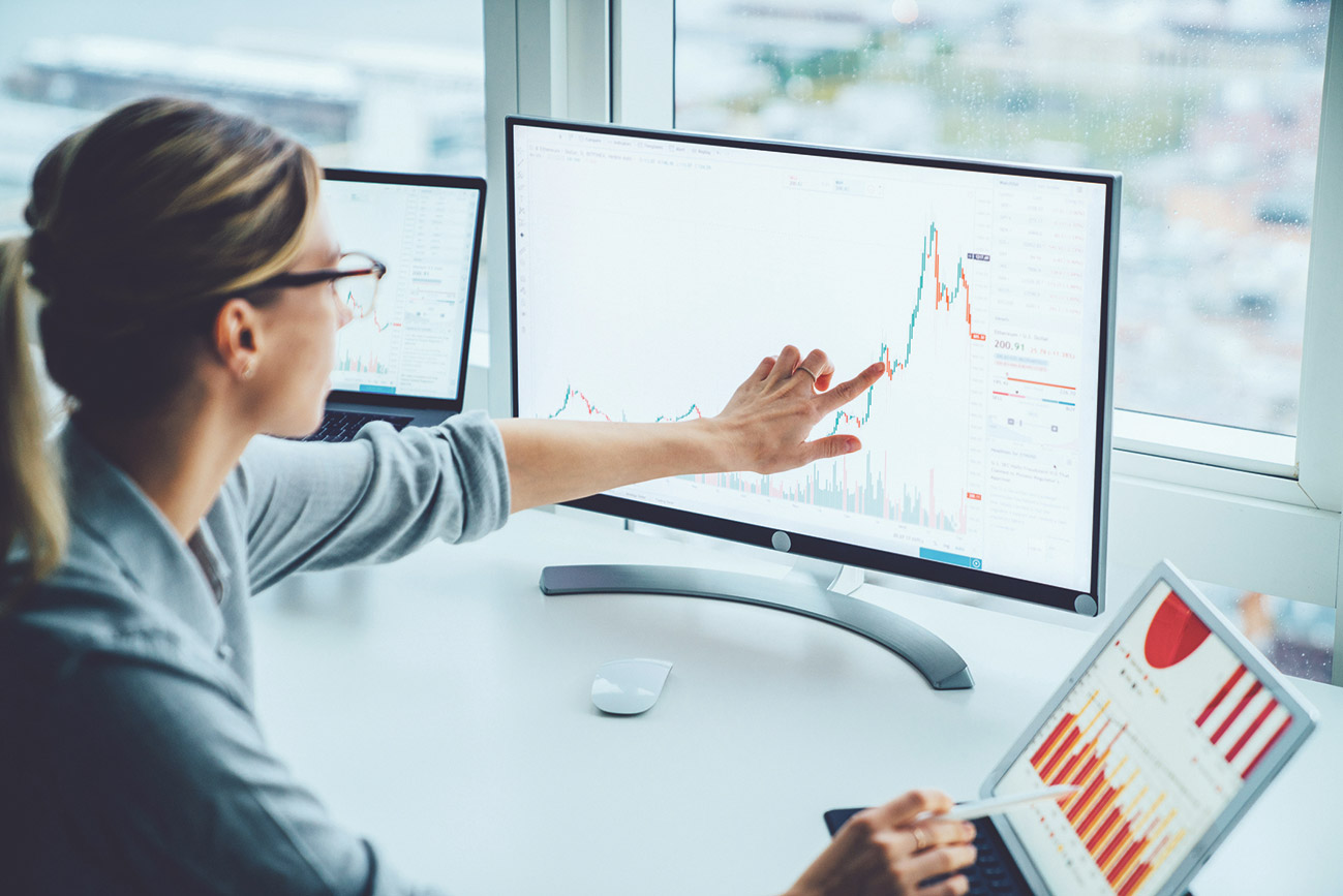 Vermögensverwalterin verfolgt die Aktienkurse am PC