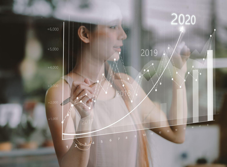 Junge Frau steht vor einer Aktienkurstafel und berechnet Prognosen
