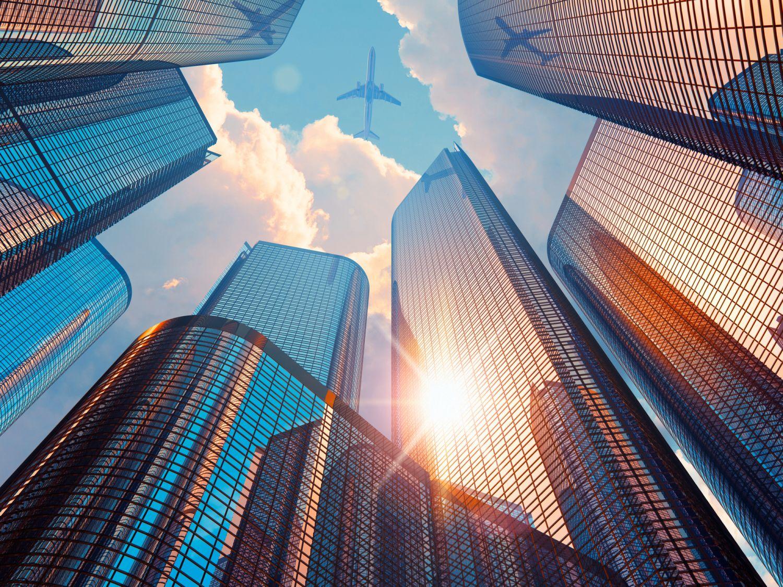 Wolkenkratzer im Sonnenuntergang, von unten gesehen. Alternative Investments umfassen auch den Bereich Immobilien