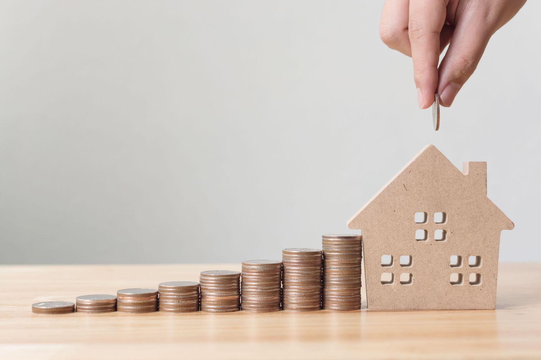 Münzstapel, die wachsen. Am Ende der Reihe steht ein Haus. Thema: Immobiliennachfrage