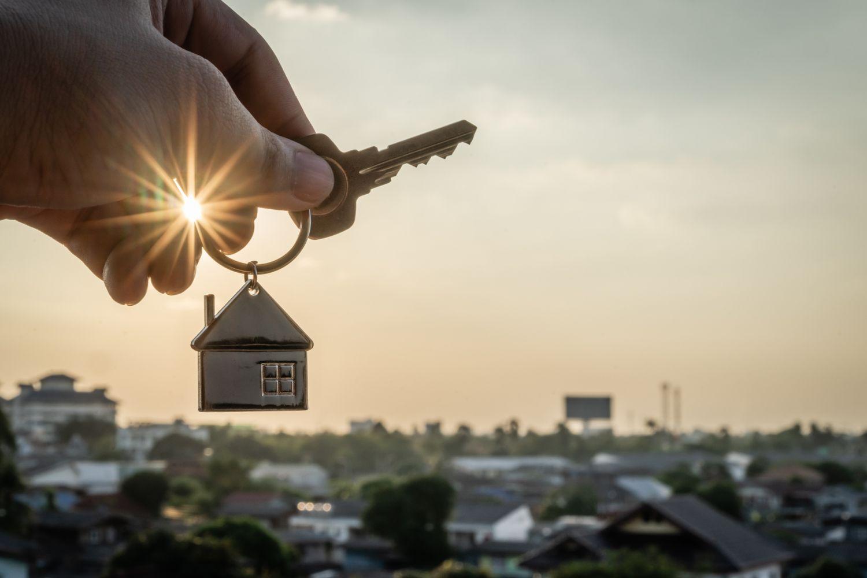 Ein Schlüssel mit einem Hausanhänger wird vor einer Stadtkulisse ins Bild gehalten.