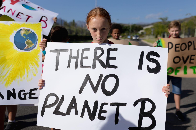 Ein junges Mädchen hält ein Streik-Plakat gegen den Klimawandel