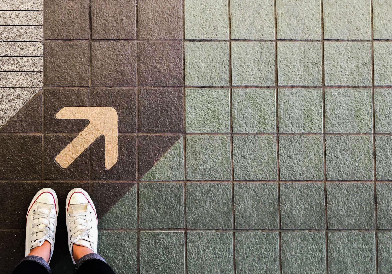 Pfeil auf dem Bodnn zeigt die Richtung an. Thema: Unternehmensleitlinien