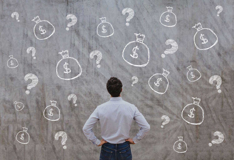 Ein Mann steht vor einer Wand, an die Fragezeichen und Geldsäcke gemalt sind. Thema: Alternative Investments