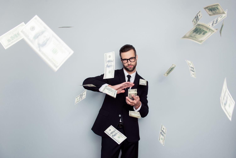 Ein Mann im Anzug wirft mit Geldscheinen um sich. Thema: Lage am Wertpapiermarkt