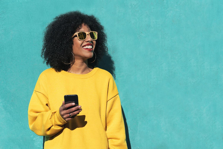 Eine Frau hält ein Smartphone. Thema: Bezahlen mit dem Smartphone