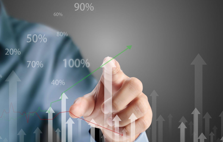 Mit Unternehmen in die Gewinnzone: Mann zeigt auf höchsten Punkt in einem Balkendiagramm