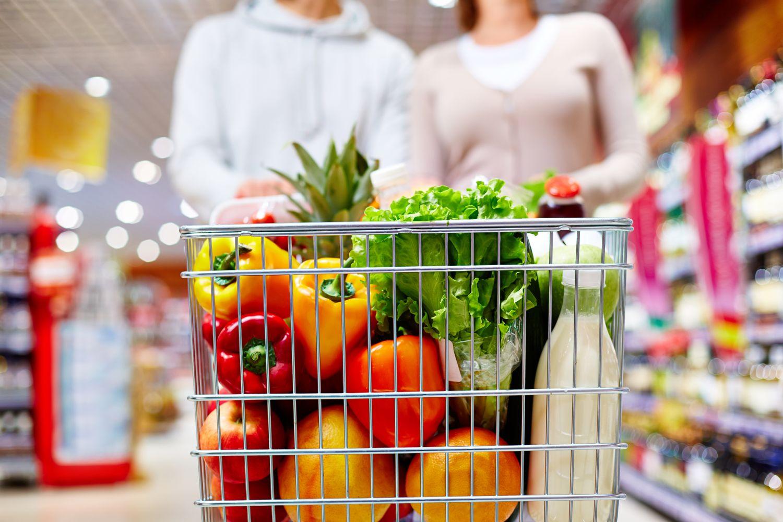 Voller Einkaufswagen mit verschiedenem bunten Obst und Gemüse.