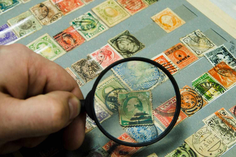 Blick mit Lupe auf Briefmarkensammlung