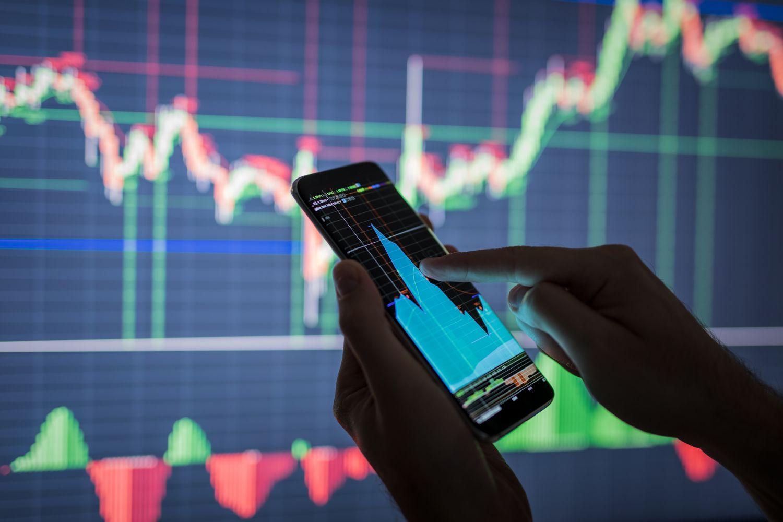 Ein Mensch prüft auf seinem Smartphone einen Aktienkurs. Thema: Aktien