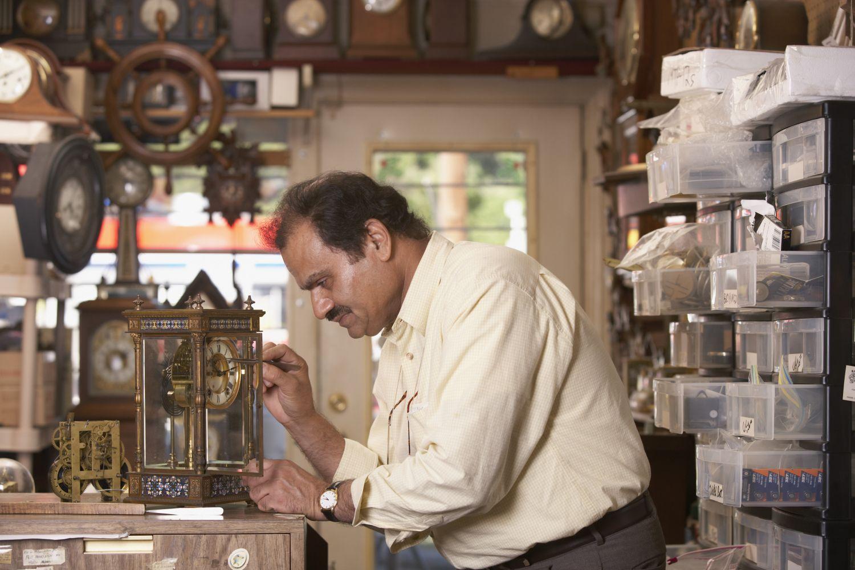 Thema Antiquitäten: Uhrmacher repariert eine alte Tischuhr.