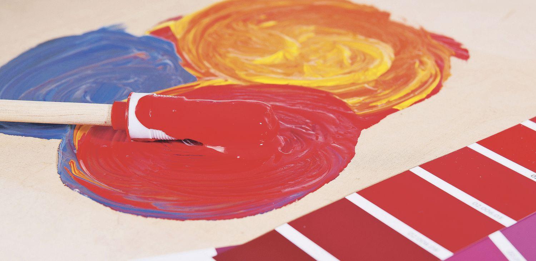 Pinsel auf Farbpalette mit roter, gelber und blauer Farbe.