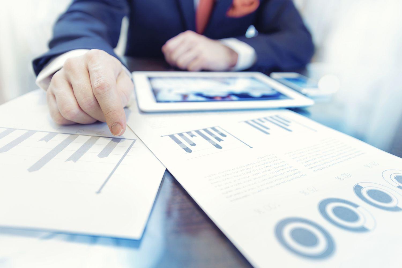 Geschäftsmann vor Tablet und ausgedruckten Charts. Thema: Geldanlage