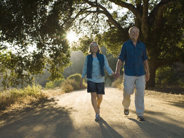 Seniorenpaar spaziert Hand in Hand bei Gegenlicht.