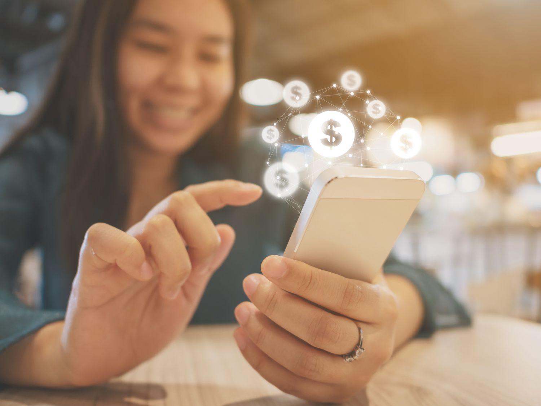 Eine junge Frau tippt auf ihr Smartphone. Thema: FinTech und Banken