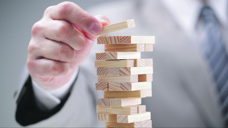 Mann stapelt Holzklötze zu Turm