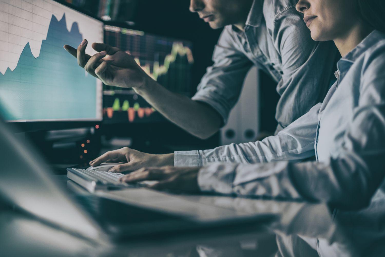 Fondsmanager schauen zusammen auf mehrere Computerbildschirme