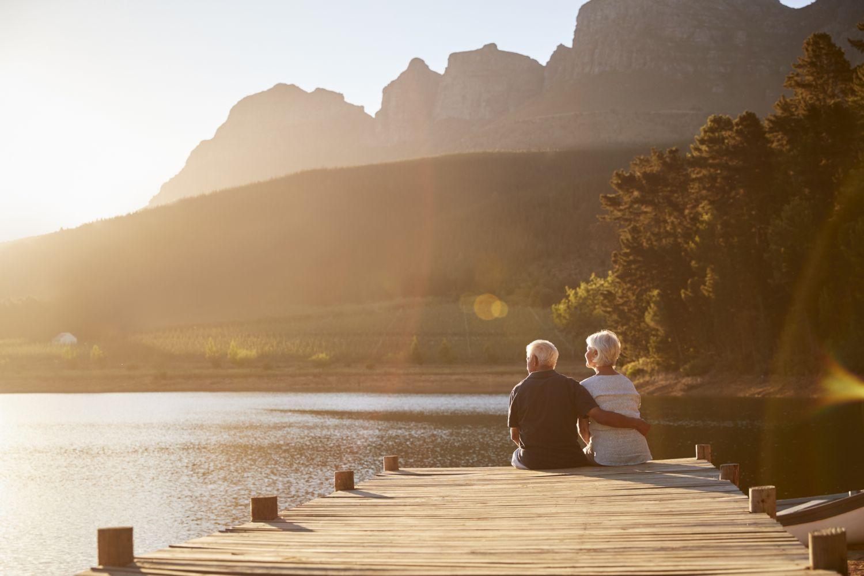 Älteres Ehepaar sitzt auf einem Steg am See. Thema: Alterssicherung