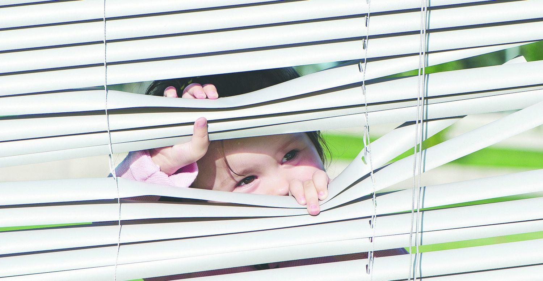 Ein Kind späht durch einen Rolladen. Thema: Vermögen von Investmentfonds