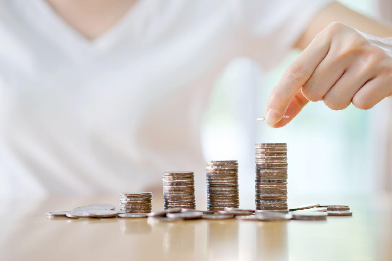 Frau verteilt Münzgeld in höher werdende Stapel. Thema: Rendite von Staatsanleihen