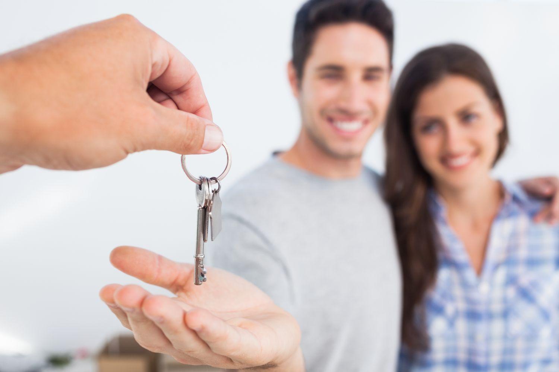 Junges Paar bekommt Schlüssel für eigene Wohnung überreicht.