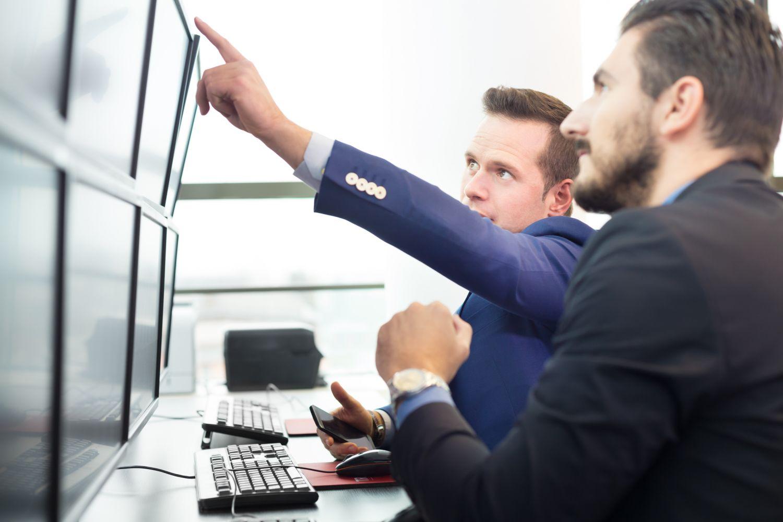 Ein Mann deutet vor einem anderen auf einen Computerbildschirm. Thema: Multi-Asset-Strategien