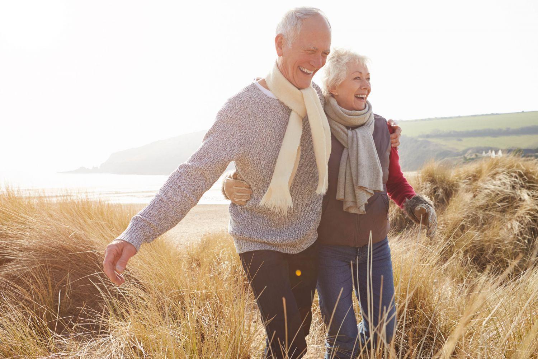 Glückliches Senioren-Pärchen geht in den Dünen spazieren.
