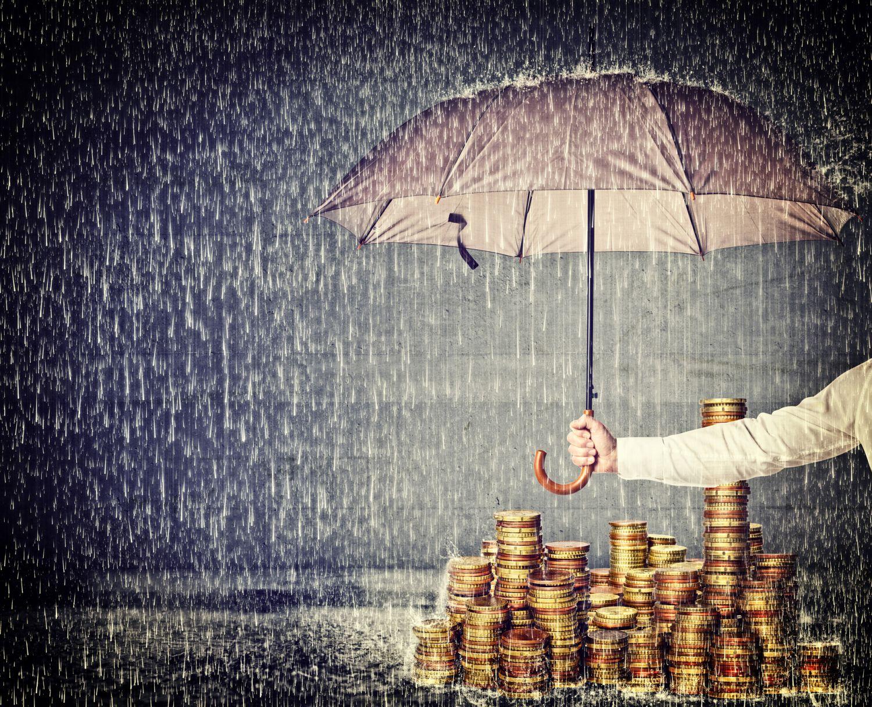 Regenschirm schützt Stapel Münzgeld vor Nässe