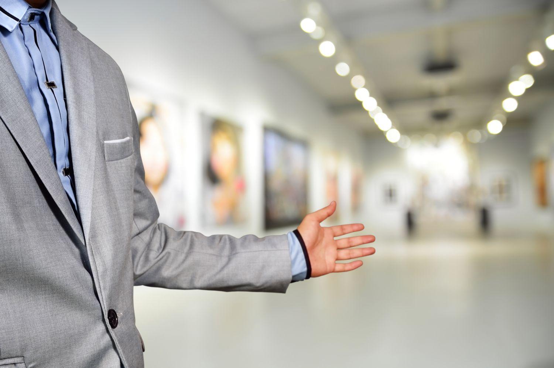 Thema: Sachwerte. Mann mit Anzug zeigt auf Kunstsammlung an den Wänden.