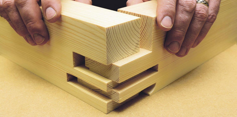 Ein Mann verbindet zwei Holzstücke. Thema: Unternehmensanleihen