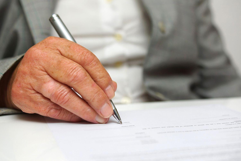 Hand beim Unterschreiben eines Dokuments.